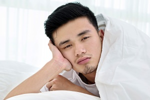Asian man awake in bed with sleepy eyes.
